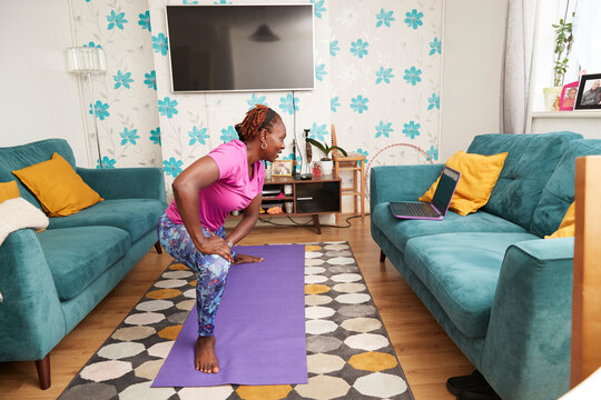 Woman practicing yoga online at laptop in living room