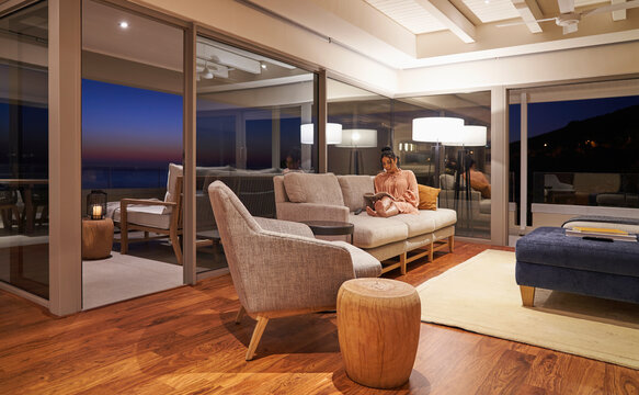 Woman relaxing and reading book in luxury living room at night