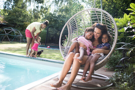 Happy mother and daughters cuddling in summer patio swing chair