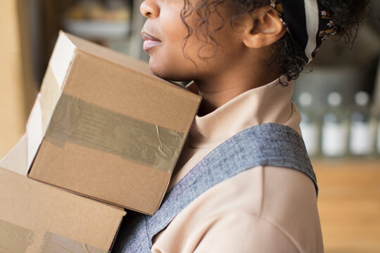 Close up female shop owner with cardboard boxes