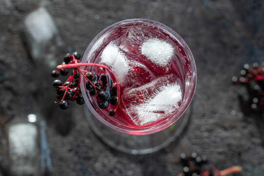Cocktail with ice and black elder syrup, decorated with elderberries