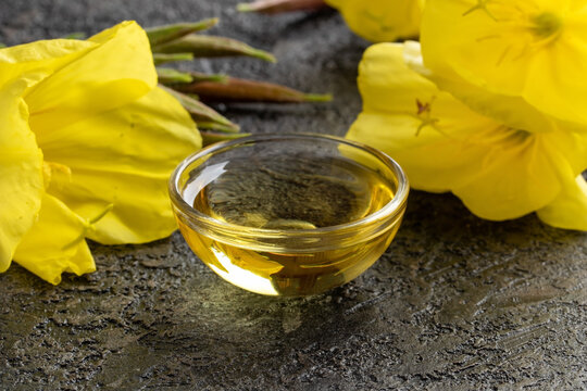 A bowl of evening primrose oil with blooming evening primrose plant