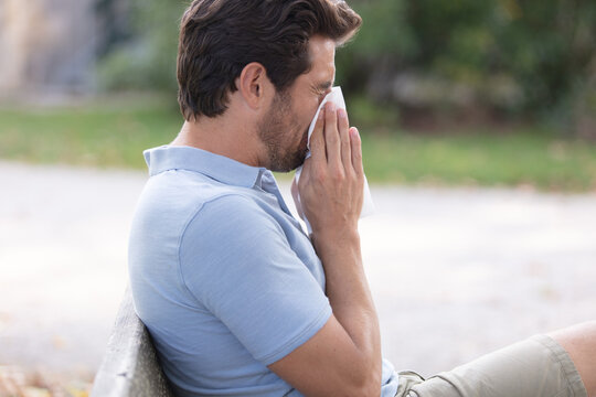 young man with allergy blowing his nose