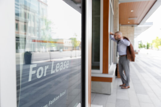 Businessman looking in window of store for lease