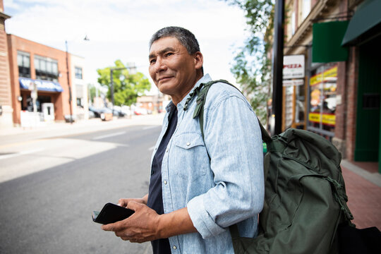 Mature man with smart phone waiting for crowdsourced taxi on sidewalk