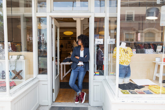 Stylish female shop owner standing in clothing boutique doorway