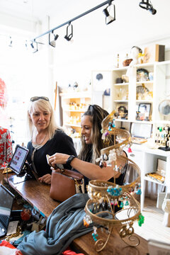 Women friends shopping and paying at boutique counter