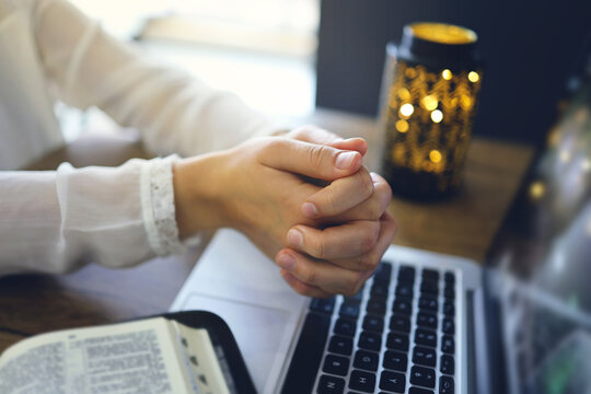 Woman praying by faith with computer laptop, Church services online concept, Online church at home concept