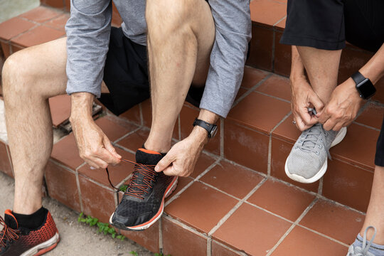 Close up couple tying running shoes on steps