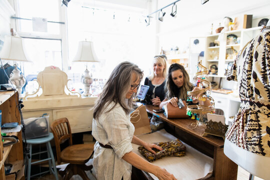 Small business owner helping customers in clothing boutique