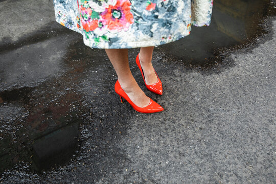 Woman in floral dress and red high heels standing between puddles