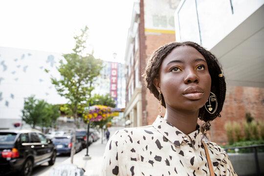 Portrait confident beautiful young woman on city sidewalk