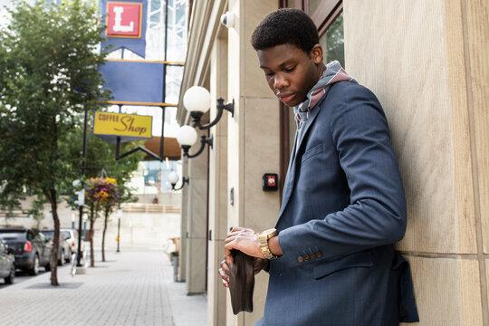 Stylish young man checking time on wristwatch on city sidewalk