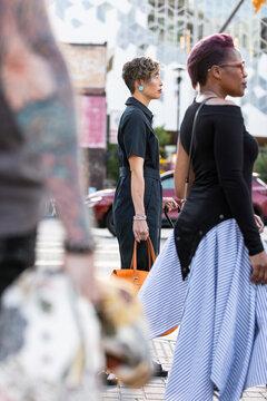 Stylish mature women waiting on city street corner