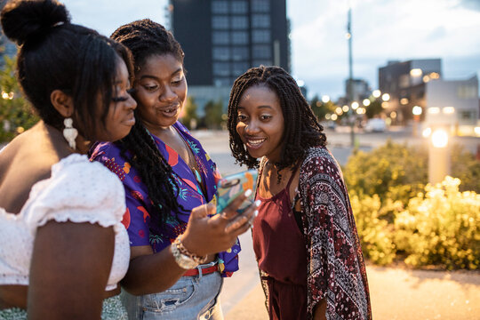 Young women friends using smart phone in city at night