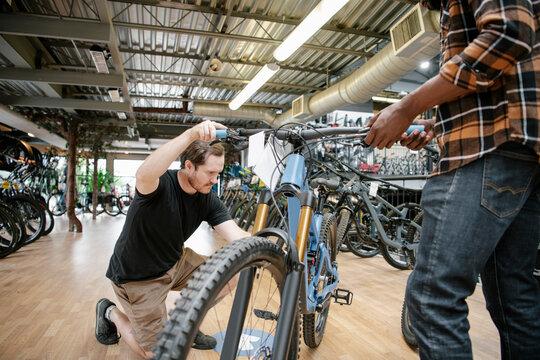 Male bike shop owner helping customer with mountain bike