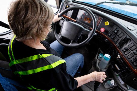 Female trucker sitting at wheel of semi truck