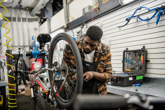 Male bike shop mechanic fixing bicycle wheel in workshop