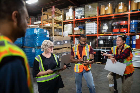 Distribution warehouse owner and workers having team meeting
