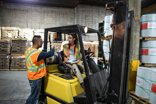Workers discussing paperwork by forklift in distribution warehouse