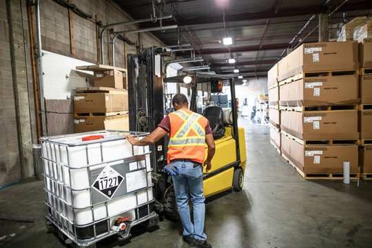 Driver checking stock on forklift distribution warehouse