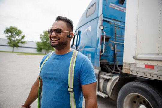 Portrait of trucker beside container semi truck