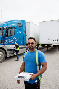 Trucker holding paperwork for container semi truck