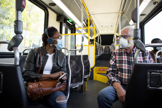 Passengers in face masks talking on public bus