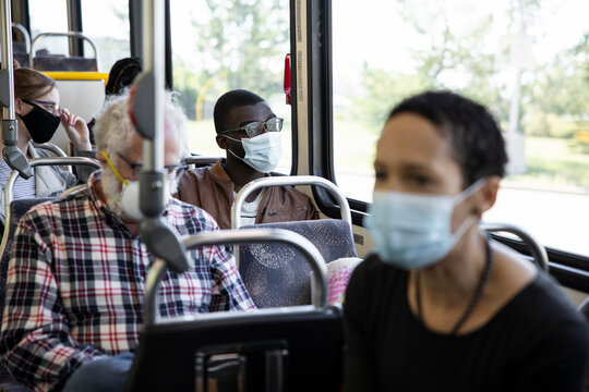 Young male passenger in face mask looking out public bus window