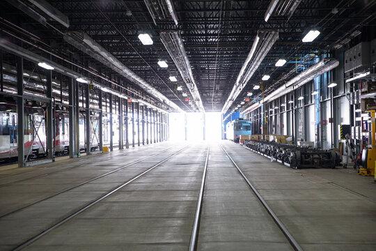 Light from windows shining on subway tracks in maintenance facility