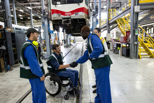 Transit engineers shaking hands in maintenance facility