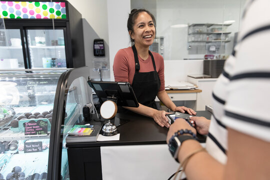 Woman serving customer paying contactlessly in cake shop