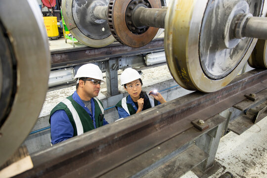 High angle view of man and woman inspecting wheel in subway train workshop