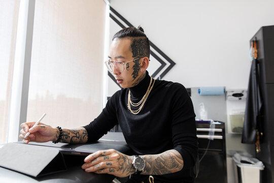 Tattoo artist designing on tablet in studio