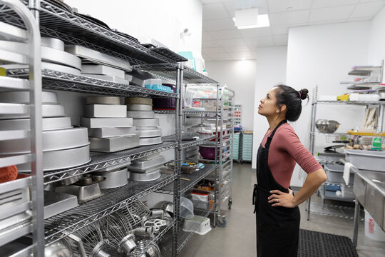 Mid adult woman looking at shelf in catering kitchen