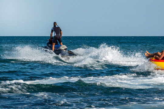 A jet ski at high speed pulls an inflatable boat with a passenger. The passenger image is cut off. Blurred into motion. Defocused image.