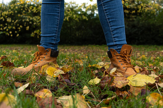 Detail picture of two yellow boots on the grass surrounded by leaves that have fallen down from the trees during the autumn season