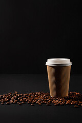Paper cup of coffee with coffee beans on black background. Side view. Take away cup.