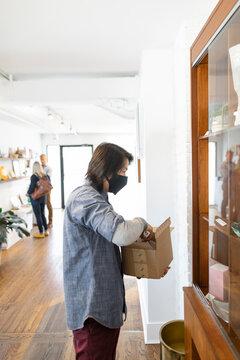 Male worker in face mask restock merchandise in marijuana dispensary