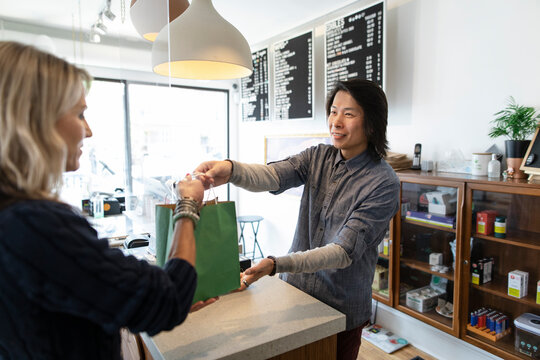 Friendly worker helping customer in marijuana dispensary