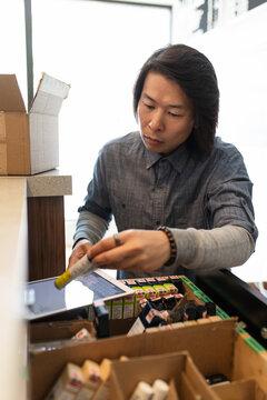 Male worker checking inventory in marijuana dispensary