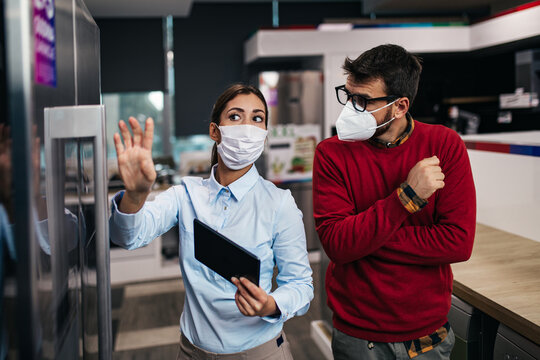 Young man talking with saleswoman about refrigerator he wants to buy. They are both with face protective masks. Pandemia, Covid-19 concept.