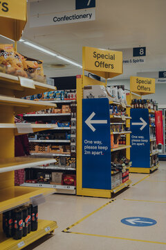 Stow-on-the-Wold, UK - July 7, 2020: One way system and social distancing signs inside Tesco supermarket due to Coronavirus pandemic, Stow on the Wold, UK.