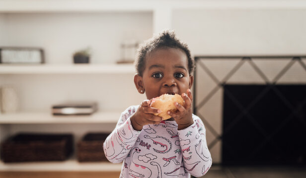 Young girl wearing purple pajamas eating donuts
