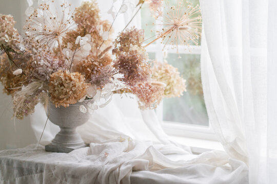 beautiful still life of dried floral bouquet in antique vase on sunny windowsill
