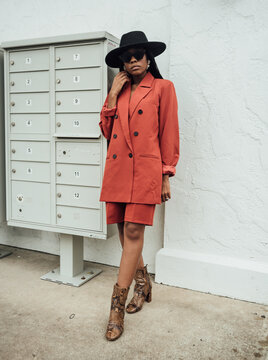 Woman in orange suit and black hat with braids standing by mailbox