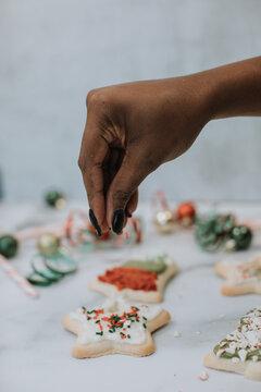 Putting Sprinkles on Christmas Holiday Cookies