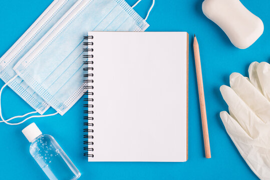 Working education study from home concept. Top layout flatlay close up photo of empty blank clear paper page open sketch pad disinfection bottle rubber gloves face surgical medical mask on table desk
