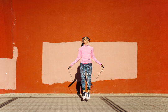 Female athlete skipping with rope on street
