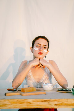 Focused young female model with cream on face at table